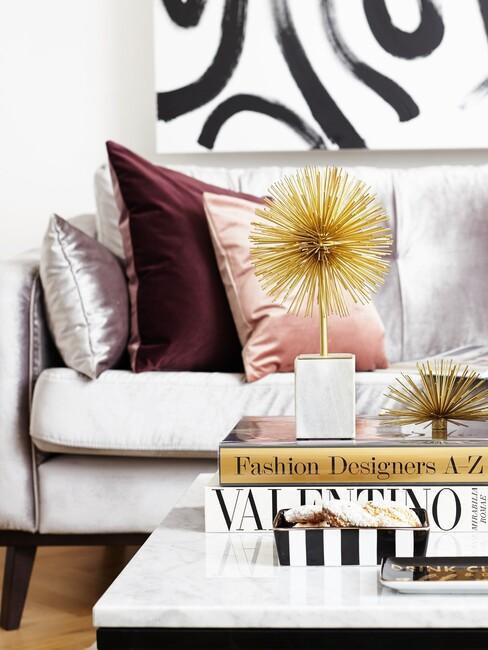grijze velvet bank met roze kussens en gouden details