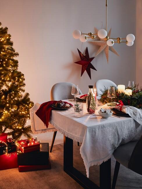 tafel met wit tafelkleed grijze stoelen en gouden hanglamp met een kerstboom