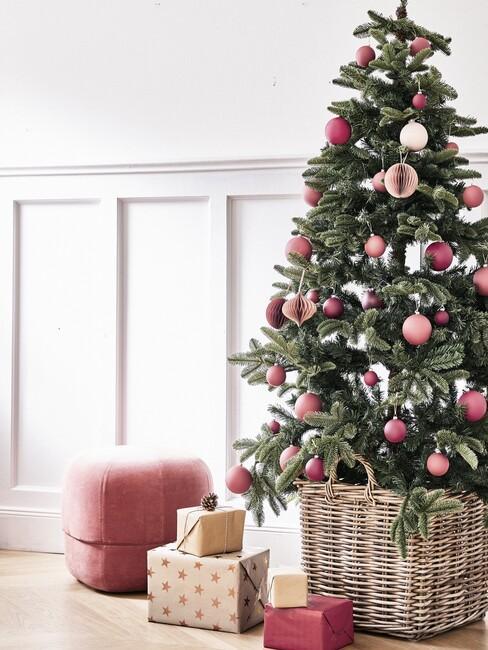 kersttrends-2021: kerstboom met roze kerstballen en roze poef