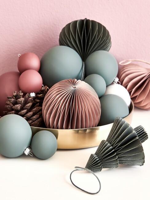 kersttrends-2021: roze met groene kerstballen op een gouden schaal