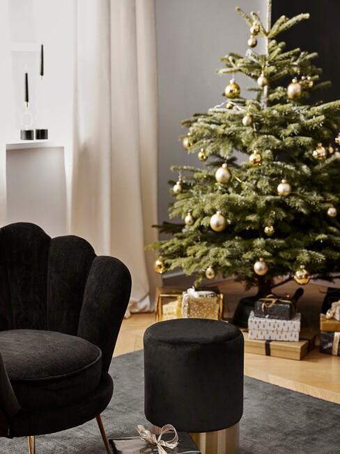 Kerstboom met witte kerstballen en zwarte stoel met gouden poten