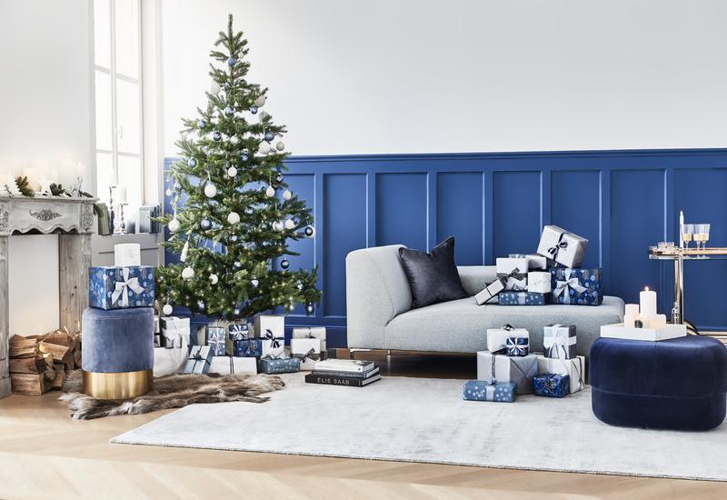 kersttrends-2021: blauwe woonkamer met grijze bank en kerstboom met blauwe kerstballen