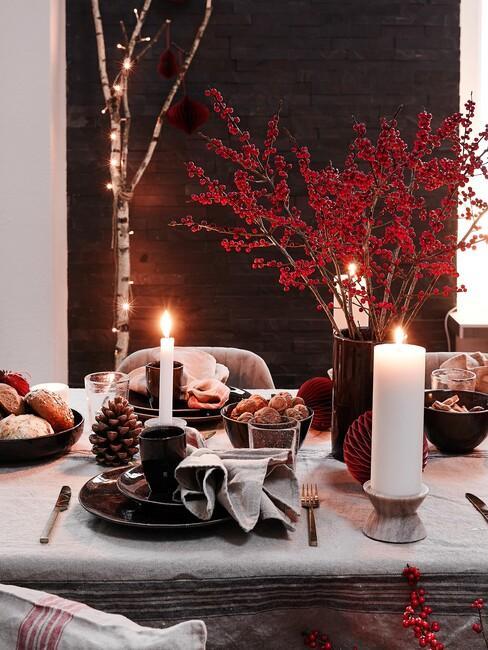 eettafel met witte kaarsen en rode bloemen