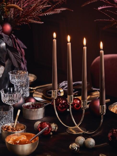 Kersttafel: gouden kaarshouders met rode kaarsen