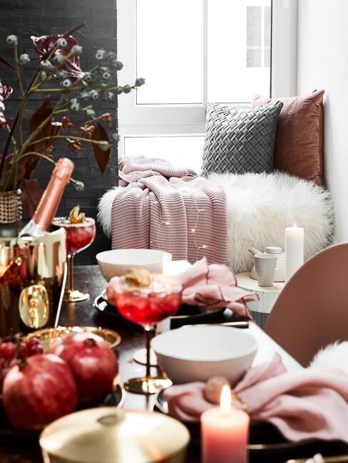 tafel met een fles wijn en rode kussens