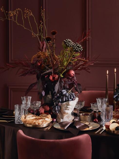 zwarte tafel met een rode stoel en witte vaas