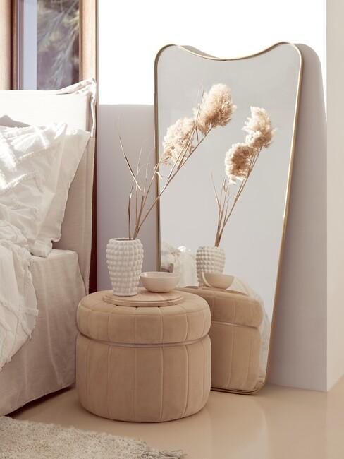 neutrale-kleuren: gouden spiegel met een beige poef