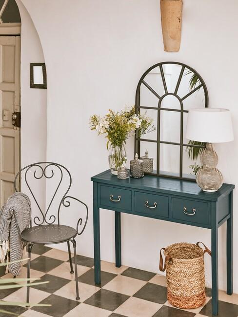 blauwe wandtafel met een spiegel met zwarte ronde tafel