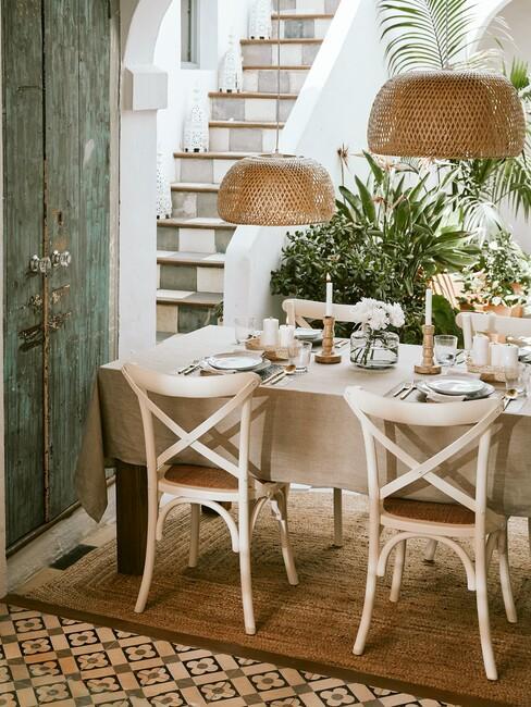 witte stoelen met houten tafel en rieten hanglampen