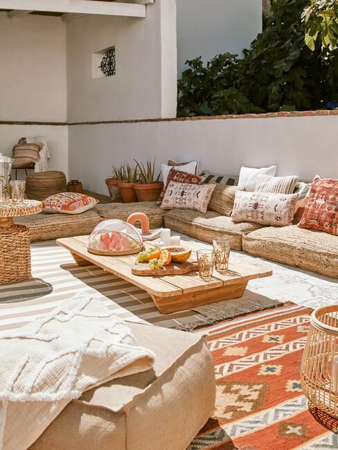 rieten vloerkussens met rood vloerkleed en houten salontafel