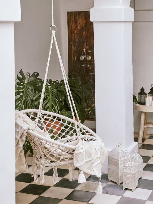 beige hangstoel boven een zwart wit geruiten vloer