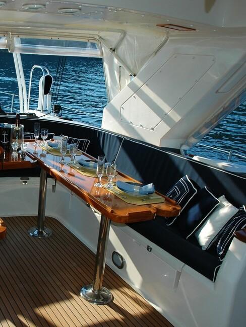 maritiem-interieur: bootdek met blauwe kussens en houten tafels