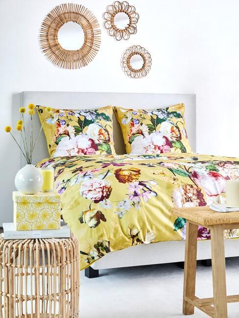 Geel bloemendekbed met een beige boxspring en houten kruk