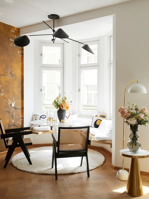 okergeel behang met een ronde eettafel en houten stoelen