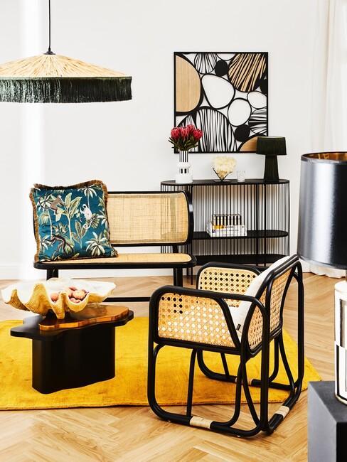 Geel vloerkleed met een houten bankset en zwarte lamp