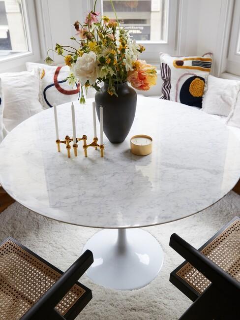 Ronde witte eettafe; ,et een zwarte vaas met bloemen en wit met gele kussens