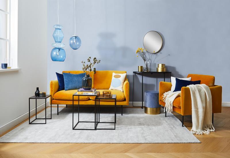Gele bank met een donkerblauwe muur en blauwe kussens
