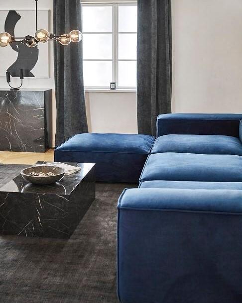 Blauwe hoekbank met een zwarte salontafel