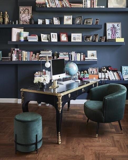 Donkerblauwe muur met een houten bureau en groene stoel