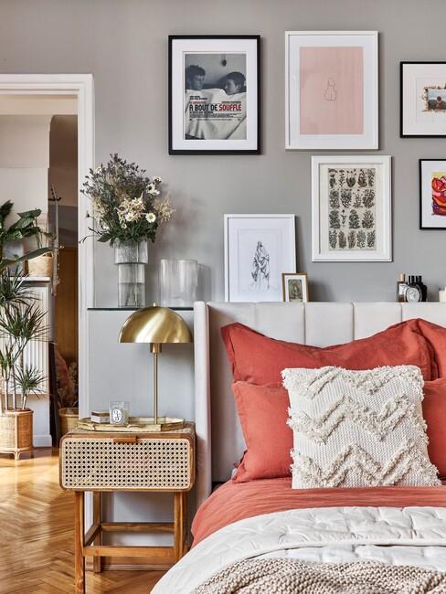 oranjerood dekbed met een beige boxspring en houten fotolijsten