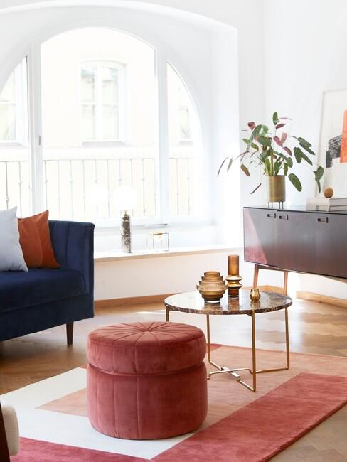 Blauwe bank met oranjerode poef en gouden salontafel