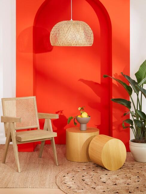 oranjerode muur met een houten stoel en een houten hanglamp