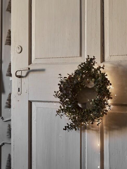 Witte deur met een groene krans