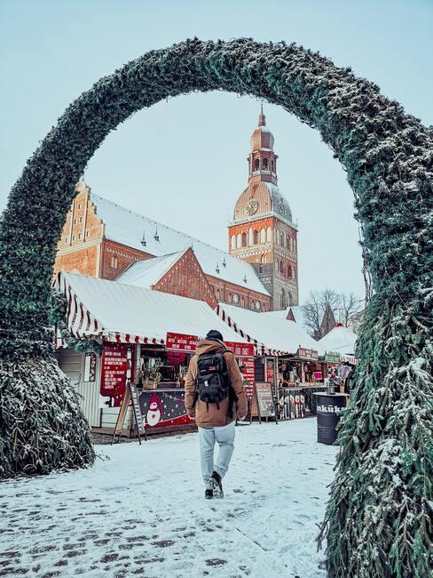 kerstmarkt met groene boog en sneeuw