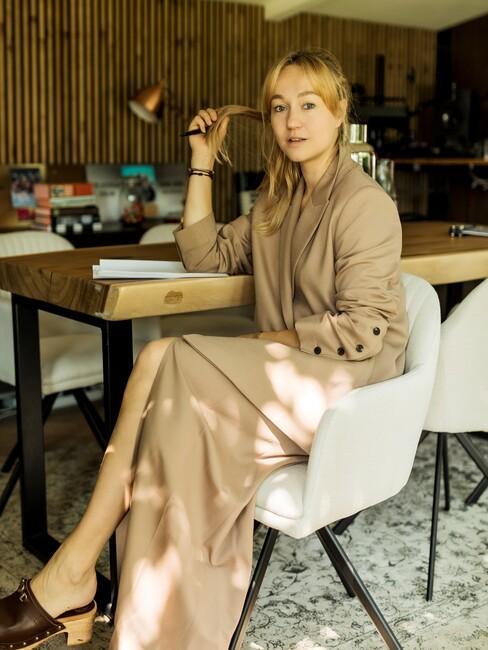 carolien-spoor: op een beige stoel aan een houten tafel