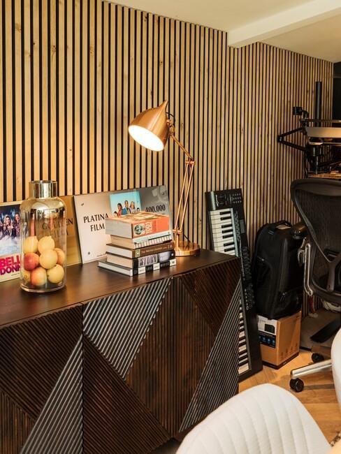 Licht houten balken tegen een muur met een donkerhouten wandtafel