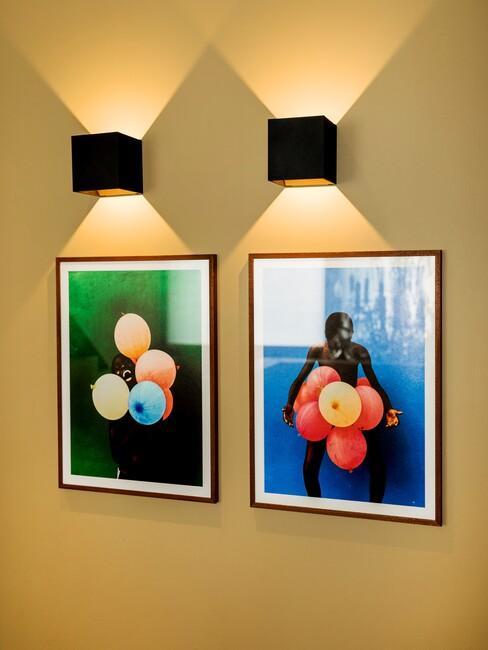 Gele muur met zwarte fotolijsten en zwarte wandlampen