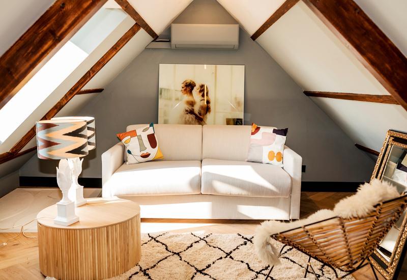 Witte bank met gekleurde kussens en houten balken