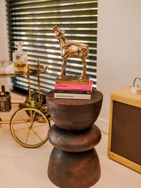 Houten bijzettafel met een gouden kalf op een stapel boeken
