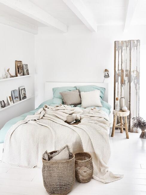 Wit bed met een mintgroen dekbed en een rieten mand