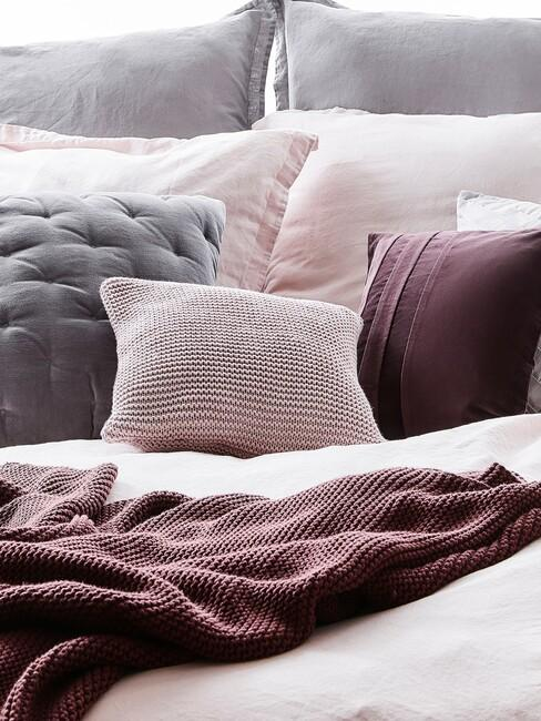 mauve kussens op een grijs bed