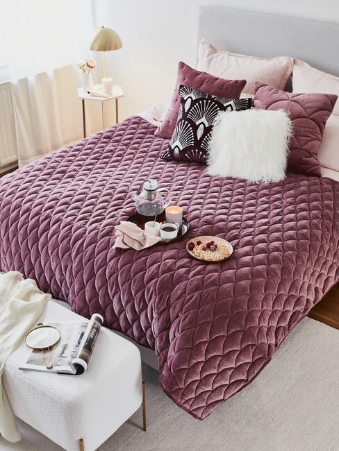 Paarse deken over een grijs bed