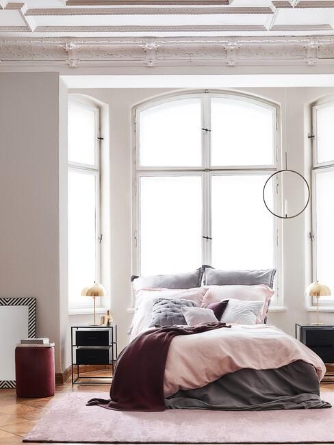 bed met roze en paarsen deken