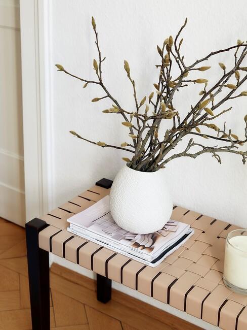 Houten bank met een witte vaas en witte muren
