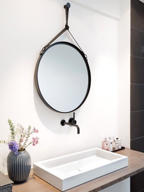 Licht houten woonkamer met zwarte ronde spiegel