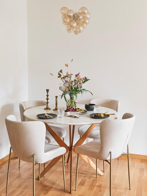 Ronde houten tafel met beige stoelen en gouden hanglamp