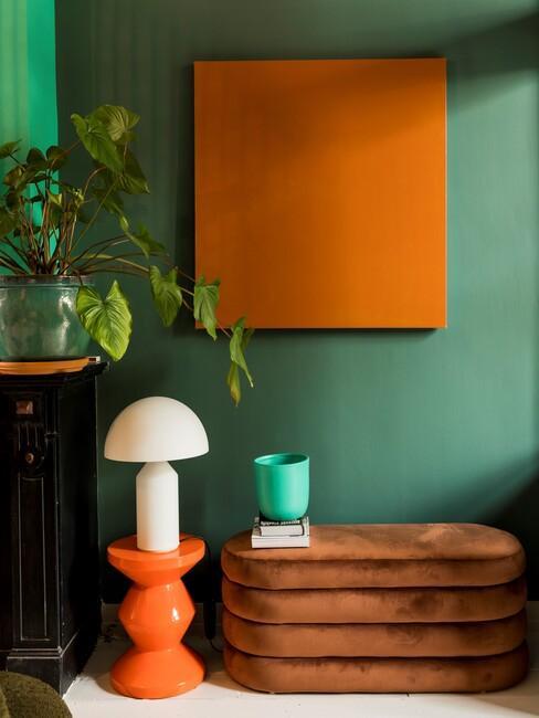 Groene muur met oranje kunst en bank