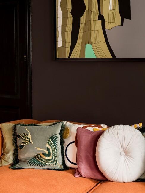 donkere-wandkleuren: zwarte muurmet oranje bank en groen kussen