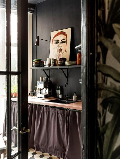Zwarte keuken met kunstwerk en houten blad