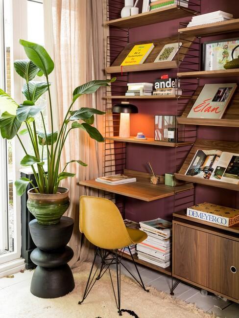 donkere-wandkleuren: donker rode muur met houten boekenkast en okergele stoel