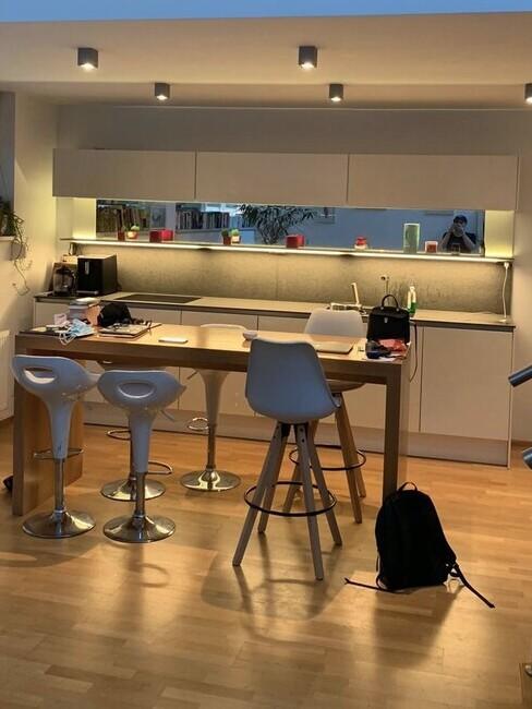 Kleine woonkamer met open keuken en bar met hoge krukken