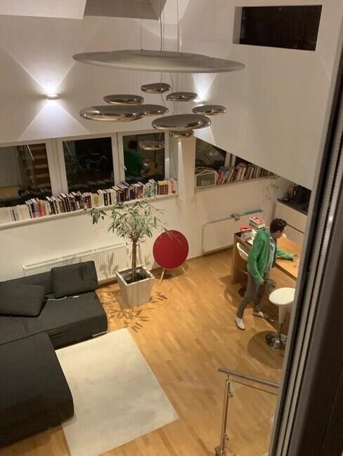 Kleine woonkamer met grijze bank en open keuken