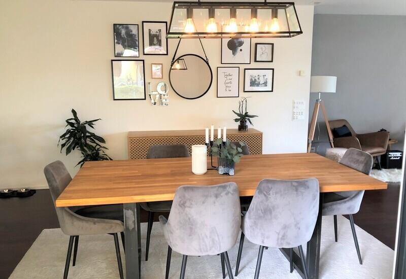 Gezellige woonkamer met houten tafel en grote hanglamp