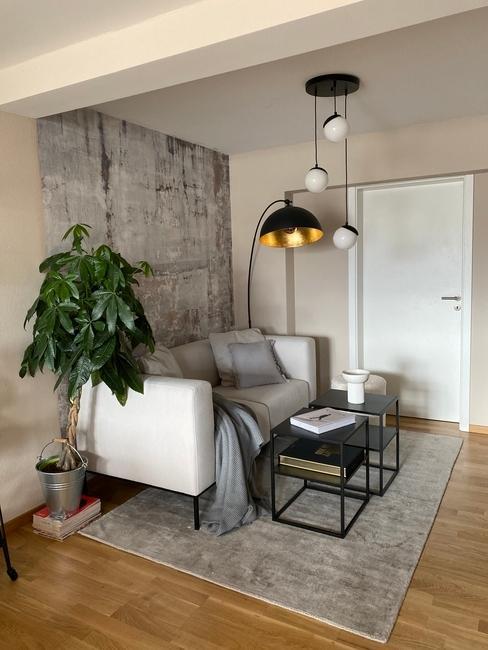 Een zithoek met lichte bank en grijs vloerkleed in klein appartement
