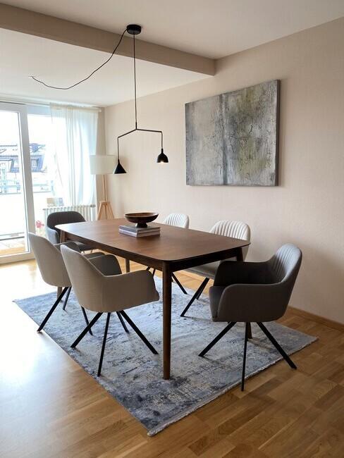 Eettafel met stoelen in verschillende grijstinten in een klein appartement