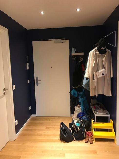 Hal in een appartement met blauwe muren, kleding- en schoenenrek